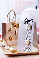Two elegantly packed gift bags decorated with upcycled bottle tops