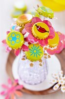Bottle caps painted yellow with various motifs used as funky centres of pastel paper flowers