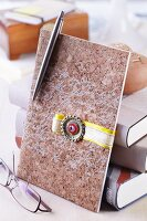 Elegant cork envelope decorated with ribbon and flattened bottle cap leaning against stack of books