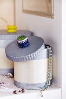 Stacked bottle tops stuck to lid of jewellery box as handle