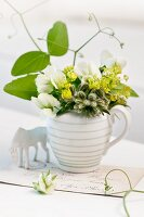Small posy of lady's mantle, borage and sugar snap pea flowers in milk jug