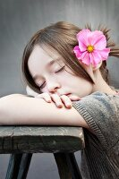 Dreaming girl with pink cosmos flower in hair