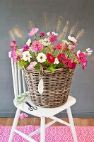 Large basket of cosmos, zinnias and fountain grass on white chair with china feather-shaped pendant