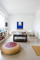 Round, basketwork floor cushion in front of black tea trolley and dining area with white classic chairs in minimalist interior