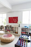 Three-dimensional game on tea trolley, two-tone floor cushion and half-height bookcase against wall in minimalist, loft-style interior