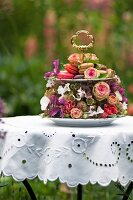 Festively decorated cake stand decorated with roses and other flowers on white broderie anglaise tablecloth in summery garden