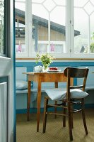Cosy restaurant with set coffee table and pale blue bench below window in renovated country house