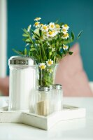 Arrangement of sugar, salt and pepper shakers and posy of chamomile on white table