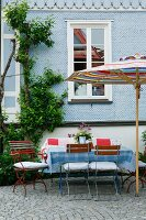 Secluded terrace seating area with parasol and garden chairs in front of pale blue clapboard facade of country house