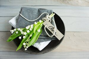 Lily of the valley and name tag on linen napkin in bowl