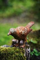 Rusty metal bird figurine on mossy tree stump