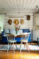 Kitchen chairs and blue bench around wooden table in rustic interior of wooden house
