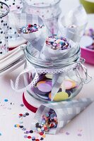 Paper cones of confetti in preserving jar