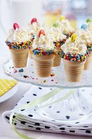 Cones of ice cream edged with sugar confetti and decorated with cream and smarties festively arranged on cake stand