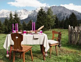 Pink candles and linen tablecloth on rustic table in summery mountain landscape