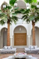Moroccan courtyard with spherical lamps above fountain and seating around palm trees in front of arcade