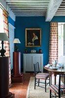 Runder Tisch und weisser halbhoher Schrank unter Frauenportrait an blauer Wand in rustikalem Esszimmer mit Holzbalkendecke