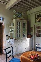 Blick über Essplatz auf weisses Küchenbuffet mit Vitrinenaufsatz in rustikalem Esszimmer mit Holzbalkendecke