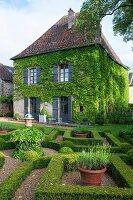 Labyrinthgarten vor beranktem Landsitz in sommerlicher Stimmung
