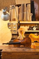 Unstrung violin amongst further string instruments on rustic workbench and assorted wood on shelf lit by retro desk lamp