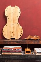 Stack of books, tuning fork, wooden shoe lasts and pale cello body leaning against dark red wall on rustic wooden surface