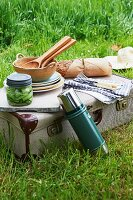 Picnic equipment, bread and salad on top of vintage suitcase