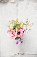 Top view of posy of pink double tulips, pink pea blossoms and dill flowers