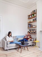 Young couple relaxing with magazine and laptop on grey sofa in renovated period apartment with wooden floor, bookcase and stucco ceiling