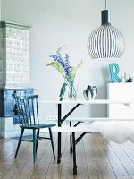 Scandinavian, designer pendant lamp above white, folding table and benches and black kitchen chair in front of tiled stove