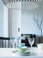 Cups and liqueur glasses on table below Scandinavian designer lamp