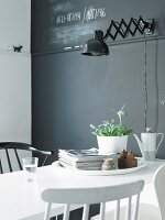 White dining table in front of grey wall with retro-style, black wall lamp