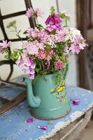 Bouquet of garden flowers in enamel coffee pot on vintage metal table