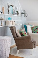 Vintage ornaments on floating shelves above white-painted wicker basket and armchairs with floral scatter cushions