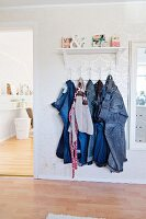 Jeans hanging from clothes rack below ornaments on shelf flanked by open door and picture frame