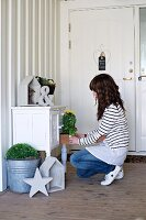 Woman decorating an antique hall cabinet with potted plants and vintage ornaments