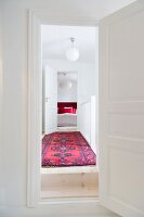 View through open interior doors along corridor with Oriental rug, spherical lamp and bedroom at far end