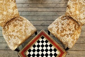 Table with integrated chess board and antique chairs with gold-patterned upholstery on rustic wooden floorboards