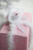 Wrapped gift decorated with star & feathery ribbon