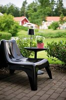 Black plastic easy chair next to black table lamp on side table on terrace