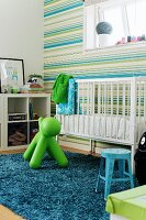 Blue long-pile rug and plastic animal hopper in front of white cot against wallpaper with horizontal stripes