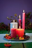 Candles and autumn berries of different colours on pewter plate
