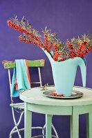 Arrangement of sea buckthorn branches in watering can on table