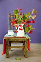 Autumnal branches of viburnum berries in enamel jug on rustic chair