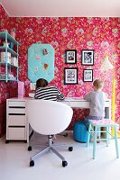 Girl and boy seated at desk in retro child's bedroom with pink floral wallpaper