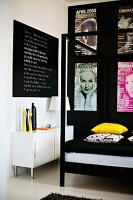 Detail of four-poster bed with black metal frame and yellow and patterned scatter cushions below collection of posters on black wall