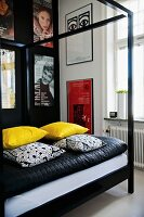 Four-poster bed with black metal frame, yellow and black and white scatter cushions on blanket and collection of posters on wall