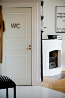 Open corner fireplace next to white interior door with WC sign