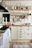 White country-house kitchen with floating wooden shelves of crockery