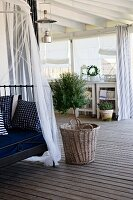 Metal day bed with cushions and canopy next to small tree in basket on wooden veranda