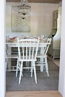 Set table and white wooden chairs in rustic dining room seen through open door